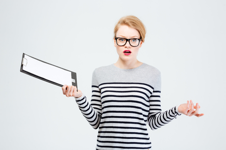 shrugging: Woman holding clipboard and shrugging shoulders isolated on a white background