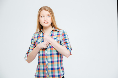 nervousness: Scared woman standing isolated on a white background