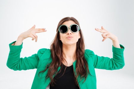 Playful pretty young woman in green jacket and round sunglasses pointing on herself with both hands over white background Stock Photo