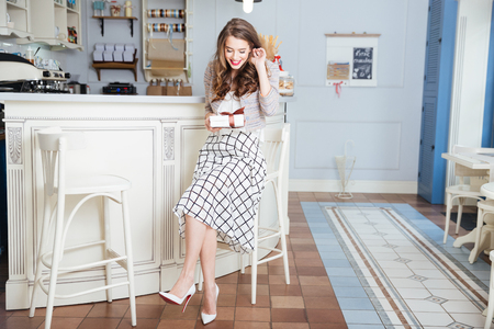 wondered: Happy beautiful young woman sitting in cafe and holding gift Stock Photo