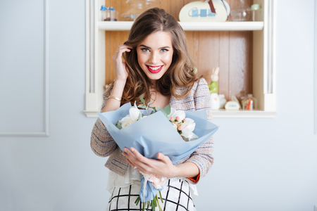 Portrait of happy cute young woman with bouquet of flowers in cafe