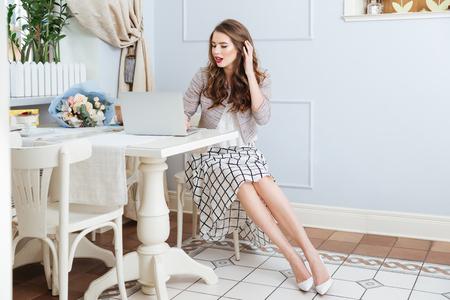 Charming glückliche junge Frau, die am Tisch mit Laptop im Café