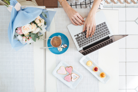Top view of hands of young woman using laptop at the table in cafe Stock Photo