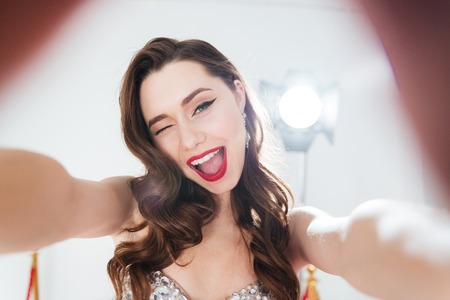 Cheerful woman winking and making selfie photo
