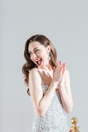 Cheerful fashion woman clapping hands isolated on a white background