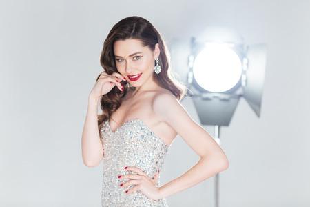 Glückliche Frau in Mode Kleid posiert mit Flash-Box auf den Hintergrund Standard-Bild