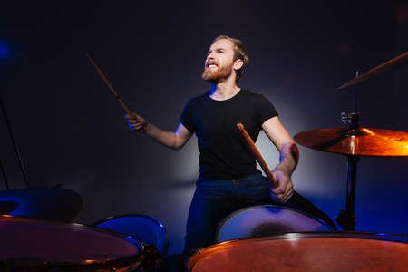 Brutal excited young man drummer with beard playing drums over dark background
