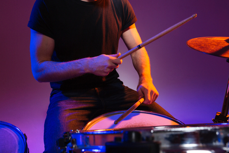 Closeup of hands of man drummer sitting and playing drums with drumsticks over dark background