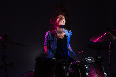 drumset: Cheerful woman playing the drums