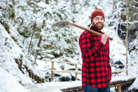 Young man holding shovel outdoors with snow on background Stock Photo