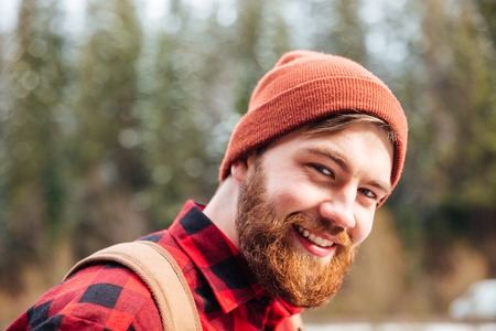 look pleased: Portrait of happy handsome young man with beard in hat and checkered shirt outdoors