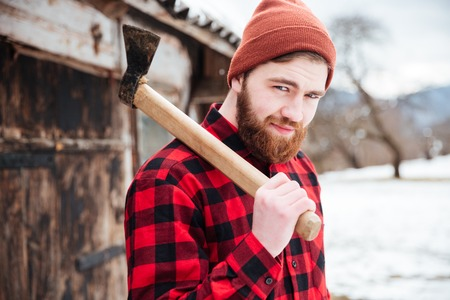 axe: Smiling bearded man in checkered shirt and hat holding axe Stock Photo