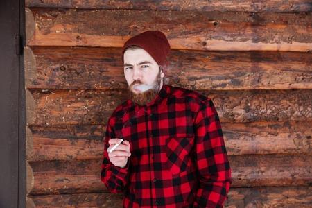 hombre fumando: fumar hermoso del hombre en fondo de madera