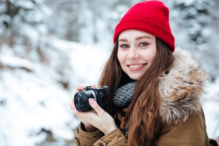 winter photos: Portrait of happy beautiful young woman photograher holding camera and taking photos in winter forest