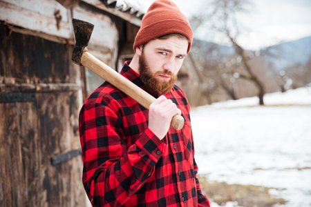 village man: Portrait of handsome bearded man with axe in village