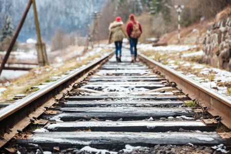 far away: Back view of beautiful young couple walking far away on railroad together Stock Photo