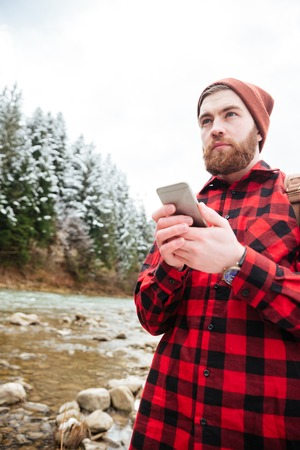 Handsome man using smartphone outdoors with river on background