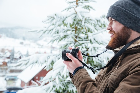 winter photos: Profile of focused young man using camera and taking photos in winter