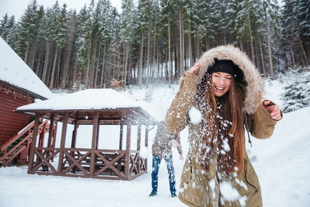 neve palle: Cheerful young couple playing snowballs and having fun near the house in winter forest