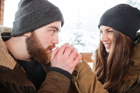careful: Handsome careful bearded young man warming his girlfriend hands in winter