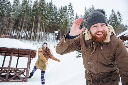 neve palle: Happy young couple playing snowballs in winter forest Archivio Fotografico