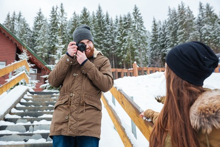 winter photos: Smiling bearded young photographer taking photos of young woman on stairs in winter forest