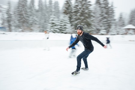 Handsome patinage homme de glace en plein air avec de la neige sur fond Banque d'images - 55113307