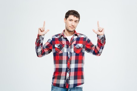pointing finger up: Young man pointing finger up isolated on a white background