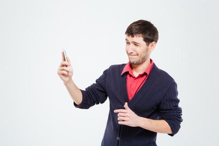 nerveux: Nerveux homme utilisant t�l�phone intelligent isol� sur un fond blanc