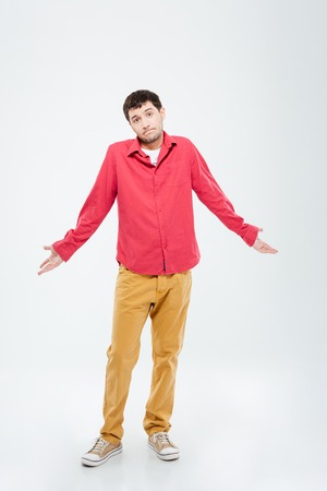 oblivious: Full length portrait of a young man shrugging shoulders isolated on a white background