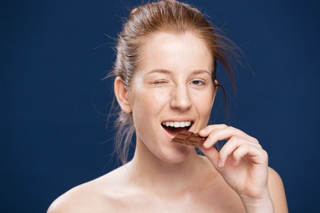 glutton: Woman eating chocolate over blue backgorund