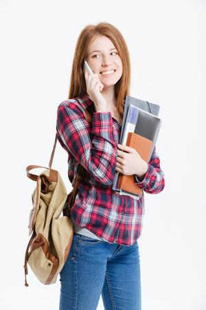幸せの女子学生が白い背景で隔離の電話で話しています。 写真素材