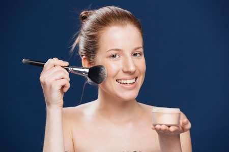 tonal: Smiling woman applying tonal cream over blue background