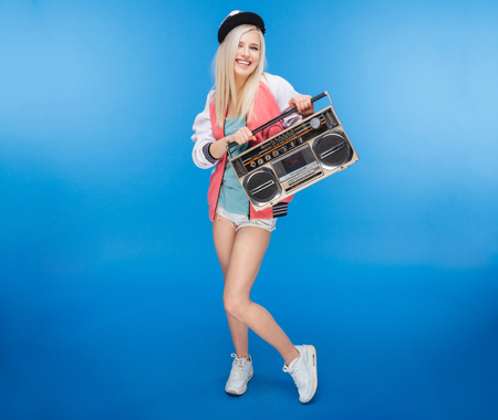 boom box: Full length portrait of a smiling female teenager holding retro boom box on blue background Stock Photo