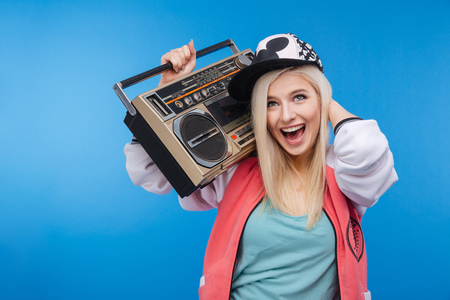 boom box: Cheerful young woman holding retro boom box on blue background
