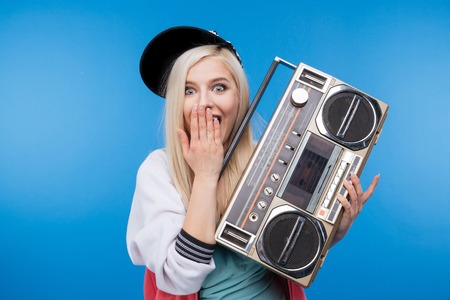 boom box: Happy female teenager holding retro boom box on blue background