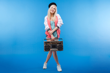 boom box: Full length portrait of a happy female teenager holding retro boom box on blue background Stock Photo