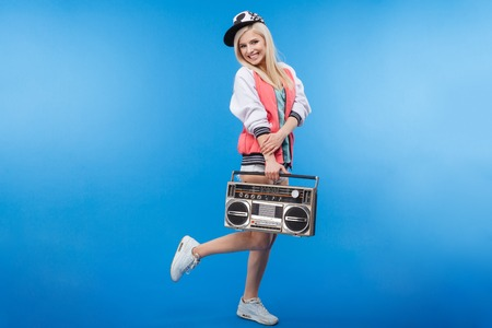 boom box: Full length portrait of a smiling woman holding retro boom box on blue background