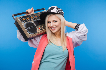 boom box: Smiling female teenager holding retro boom box on blue background