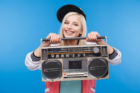 boom box: Smiling young woman holding boom box over blue background Stock Photo