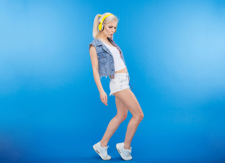one people: Full length portrait of a stylish female teenager dancing over blue background