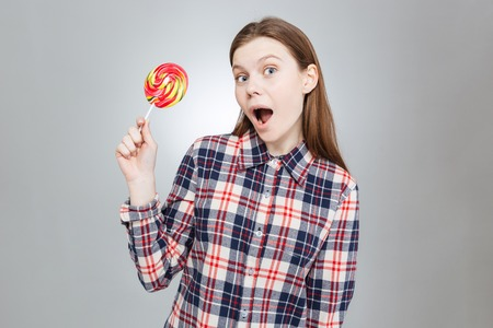 Amazed pretty teenage girl in plaid shirt with mouth opened holding lollipop