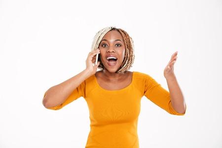 Feliz excitada joven mujer afroamericana hablando por teléfono móvil sobre el fondo blanco