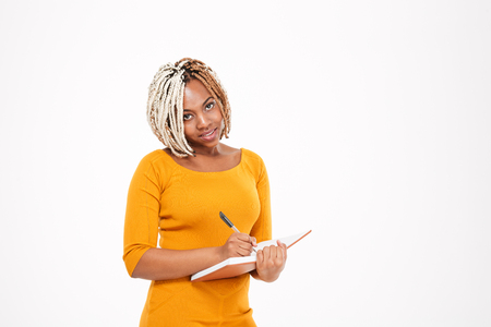 pretty dress: Pretty young african american woman in yellow dress standing and writing in notebook over white background Stock Photo