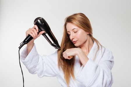 Young woman drying her hair isolated on a white background Stock Photo