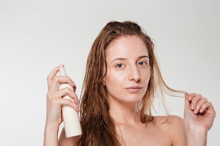 hairspray: Beautiful woman spraying hairspray isolated on a white background