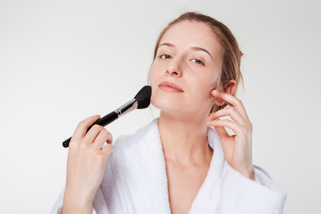 blusher: Woman applying blusher isolated on a white background Stock Photo