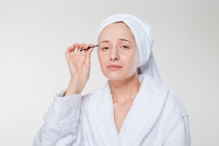 depilate: Woman in bathrobe and towel depilating her eyebrow on a white isolated background Stock Photo