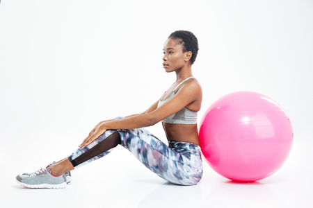 fitball: Gorgeous beautiful young african american sportswoman sitting and posing with fitball over white background