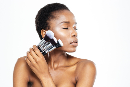 girl  care: Relaxed afro american woman with closed eyes holding makeup brushes isolated on a white background